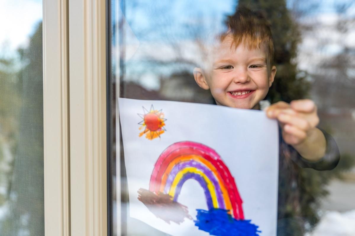 Boy putting rainbow on window