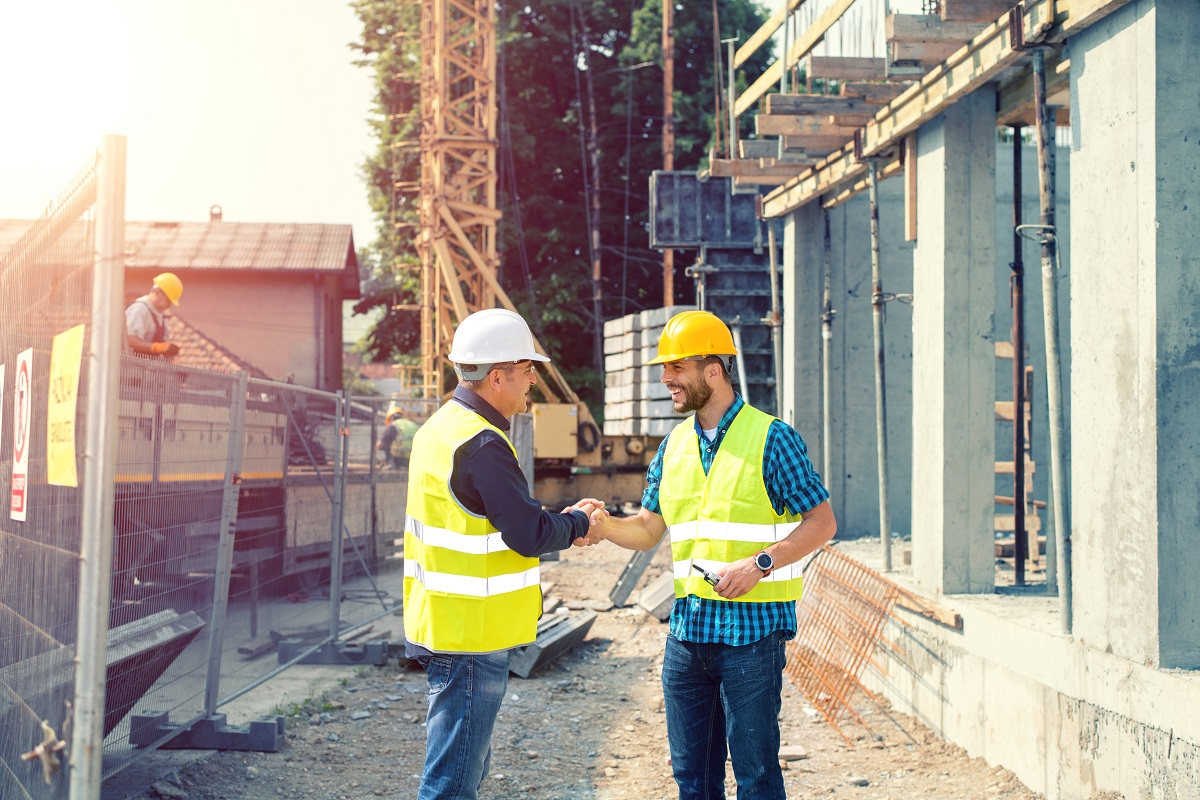 Construction workers on site smiling shaking hands