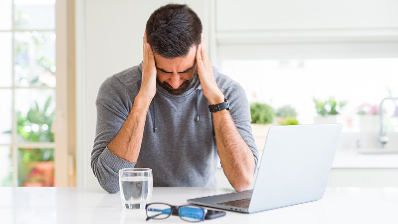 man holding head looking at laptop