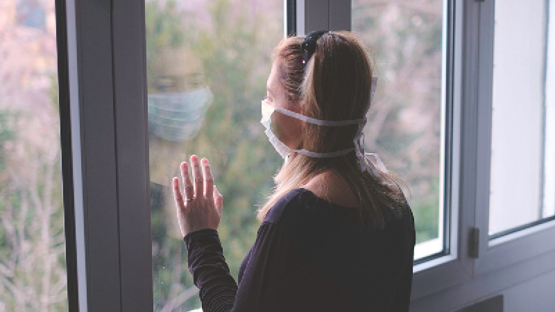 lady wearing facemask beside window